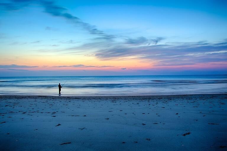 浜辺で魚釣りをしている人